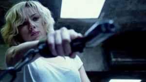 Scarlett Johansson wielding a gun in Lucy (2014).