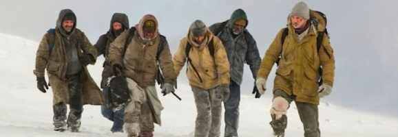 Ottway leading the other men through the cold Alaskan wilderness