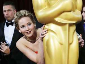 Jennifer Lawrence hiding behind an Oscar statue.