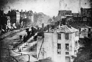 """Boulevard du Temple"" (1838) by Daguerre is believed to be the earliest photograph showing a living person. A man having his boots polished and the bootblack polishing them are at the lower left side of the image."