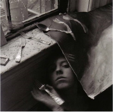 """It must be time for lunch now"" (1979) is humorous for its clever title as well as for its subject matter. A crouching Francesca, shrouded in the shadow of a thin cloth, is surrounded by eating utensils, as though they are bombarding her with the news that it is lunch time. The image's long exposure makes some of the utensils appear wispy and bent, a funny and interesting visual touch."