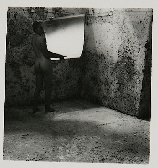 """Self-Deceit 2,"" Rome, Italy (1978). Produced while Woodman was studying in Rome, ""Self_Deceit 2"" is aesthetically notable for its strong contrast (the darkness of Woodman's figure vs. the highlight of the mirror that she is holding) and for displaying the spectral qualities that characterize Woodman's work. The image is perhaps a portrayal of Woodman's lack of faith in her ability to become noteworthy. She stands baring herself to the world, holding a large photograph-shaped mirror. The mirror, like her work is supposed to reflect herself and her talent, yet though it is cumbersome to hold up, it is still blank."