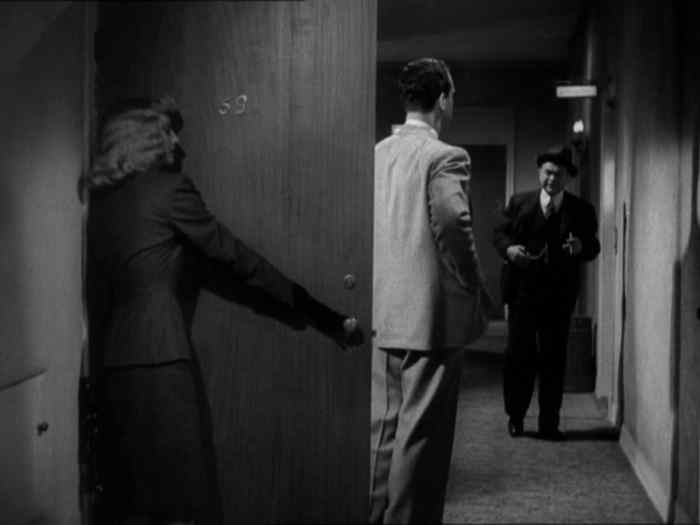 "Fred MacMurray (center) hides his lover and murderess Barbara Stanwyck behind the door of his apartment in Billy Wilder's 1944 classic ""Double Indemnity."" It is a conceit of the story that the door is hinged incorrectly."