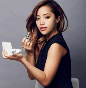 Michelle Phan with her brand of makeup, Em-Cosmetics.