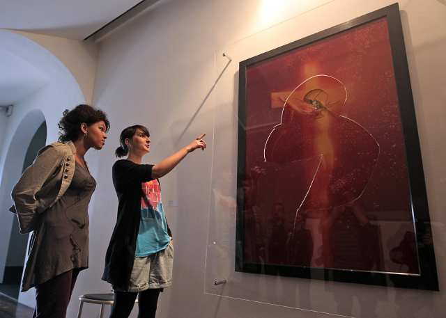 "Visitors look at ""Piss Christ"", a piece of art by U.S. artist Andres Serrano, partially destroyed by catholic activists in Avignon, April 19, 2011. The Piss Christ created in 1987, is a photography representing a small plastic crucifix submerged in a glass of the artist's urine. REUTERS/Jean-Paul Pelissier (FRANCE - Tags: SOCIETY CRIME LAW RELIGION)"
