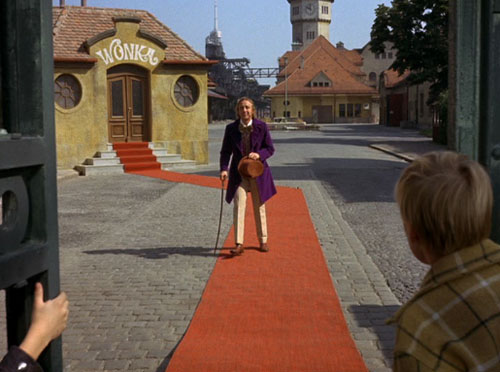 Wonka ushers his guests through the gates to begin their tour