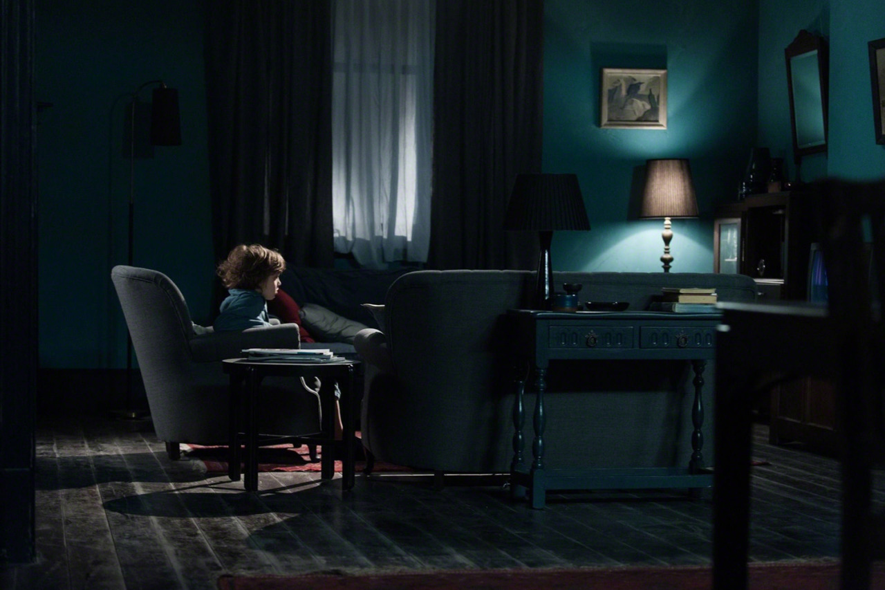 Samuel surrounded by darkness - only small amounts of light, making the atmosphere in the house stiffling