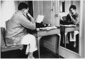 At the Dorchester Hotel, Hemingway works at his desk.