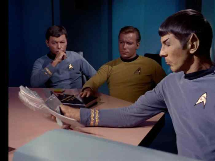 Captain Kirk consults with Spock and Dr. McCoy at the conference table.