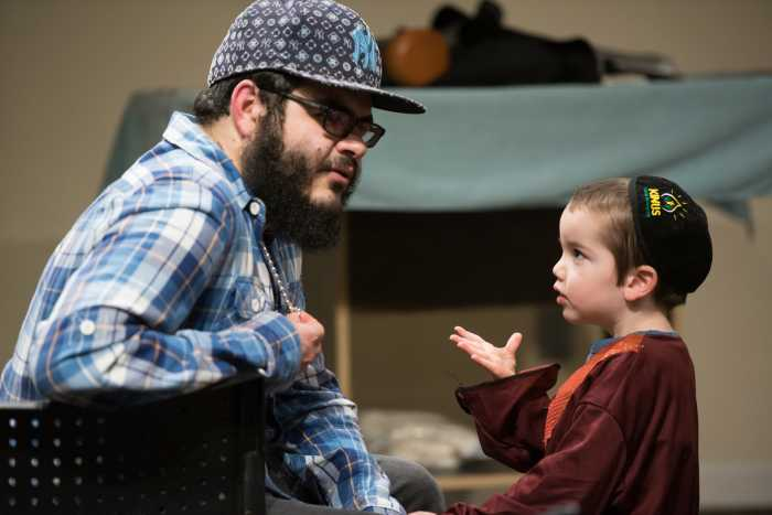 A young Orthodox Jewish child talks to a college student